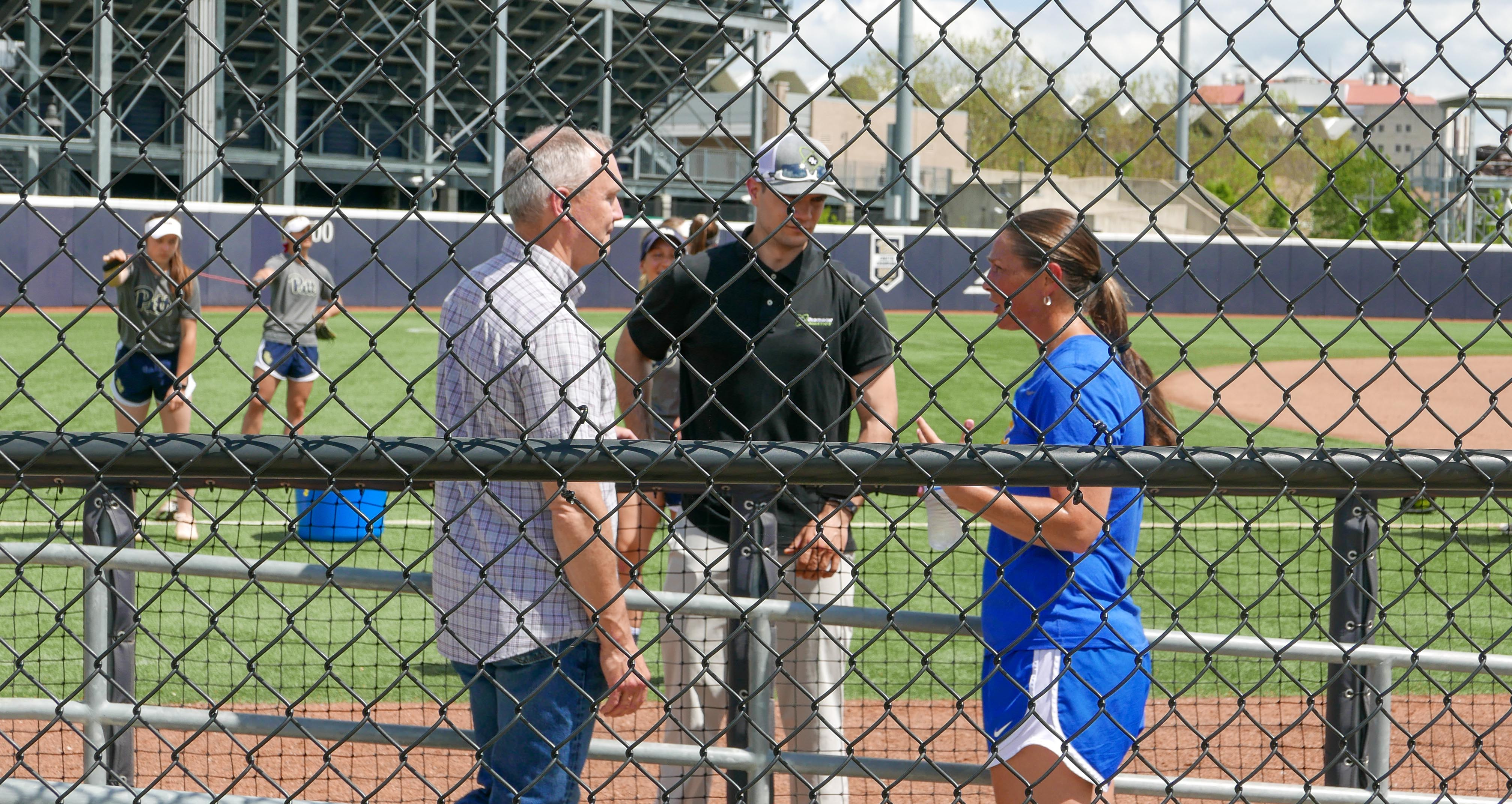 Clarks meeting with softball coach on field