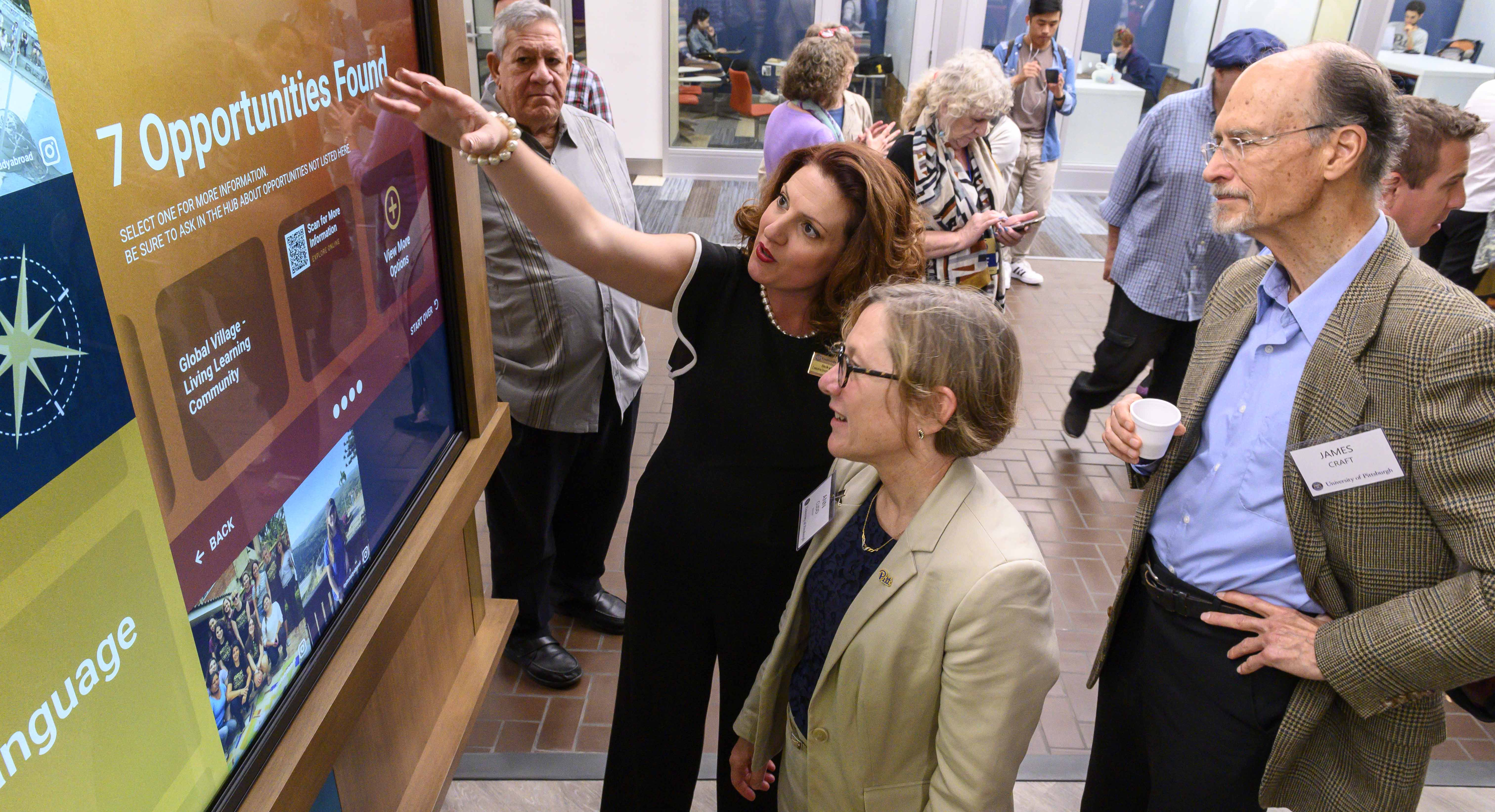 Belkys Torres shows Provost Cudd one of the interactive walls